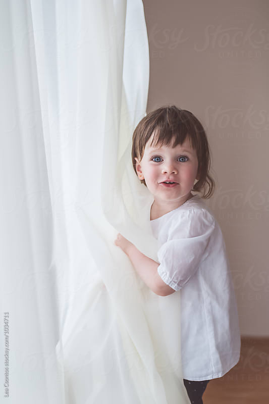 Cute little girl playing peak-a-boo behind a curtain by Lea Csontos for Stocksy United