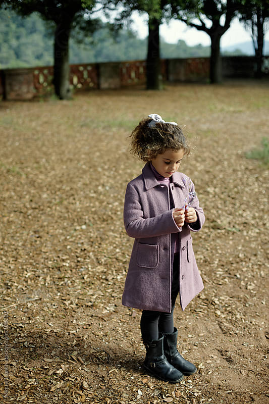 Little fashion girl holding a flower outdoors by Miquel Llonch for Stocksy United