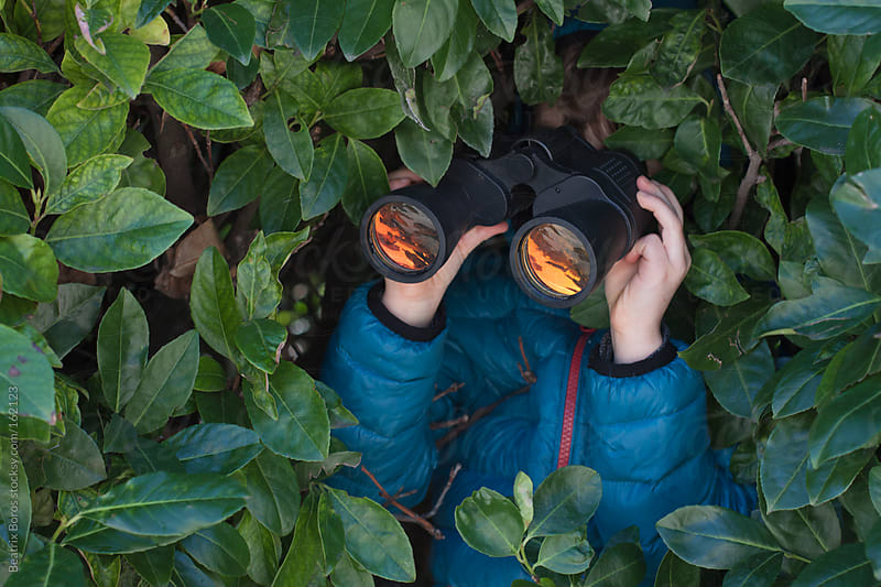 Boy hiding in the bush, watching birds with telescope by Beatrix Boros for Stocksy United