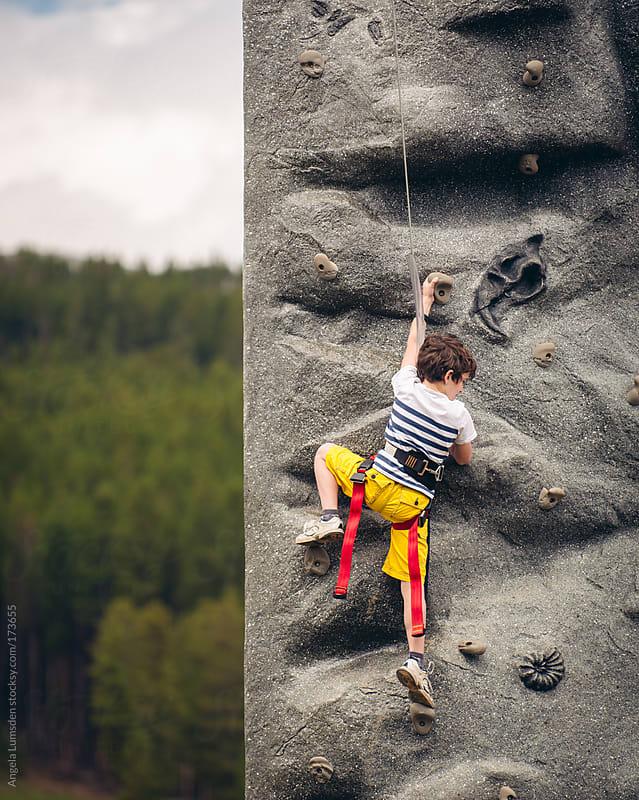 Boy climbing a rock wall by Angela Lumsden for Stocksy United