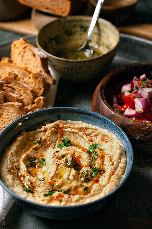 A bowl of hummus and bread and salad closeup. by Darren Muir for Stocksy United
