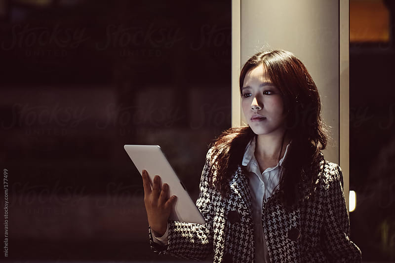 Young asian woman using a digital tablet outdoors by michela ravasio for Stocksy United