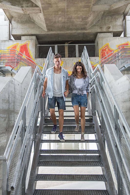 Young modern couple walking down the stairs by Jovo Jovanovic for Stocksy United