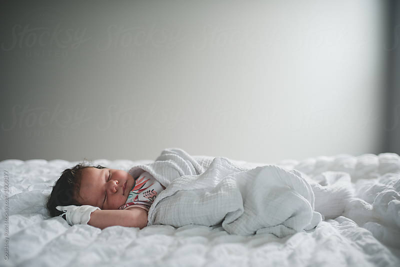 Tiny baby Asleep on a bed by Courtney Rust for Stocksy United
