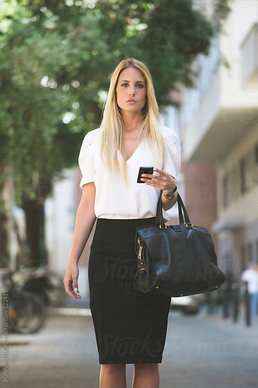 Young businesswoman with smartphone and big bag on the street. by BONNINSTUDIO for Stocksy United