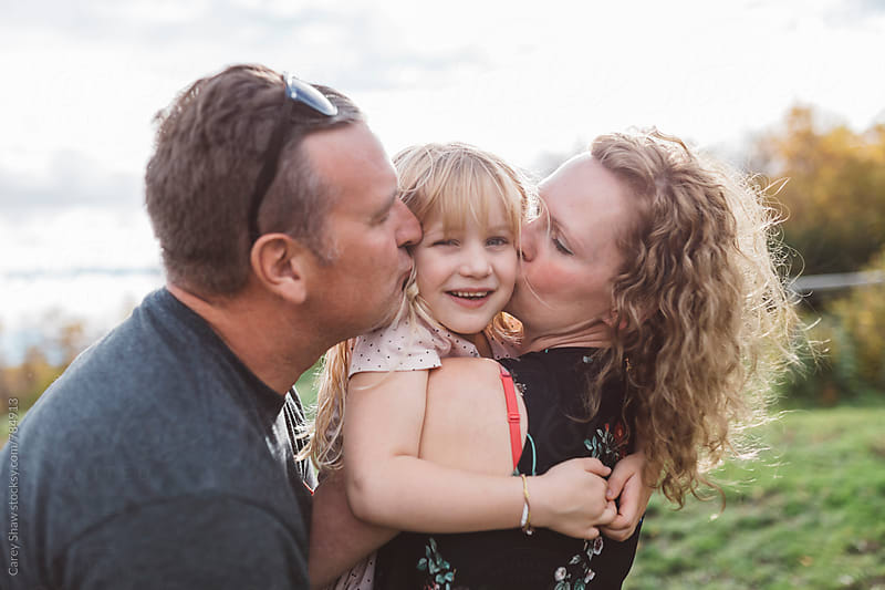 Parents cuddling with their smiling daughter by Carey Shaw for Stocksy United