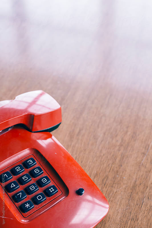 red retro phone on a wooden table,interior,style,colorful,different by Igor Madjinca for Stocksy United