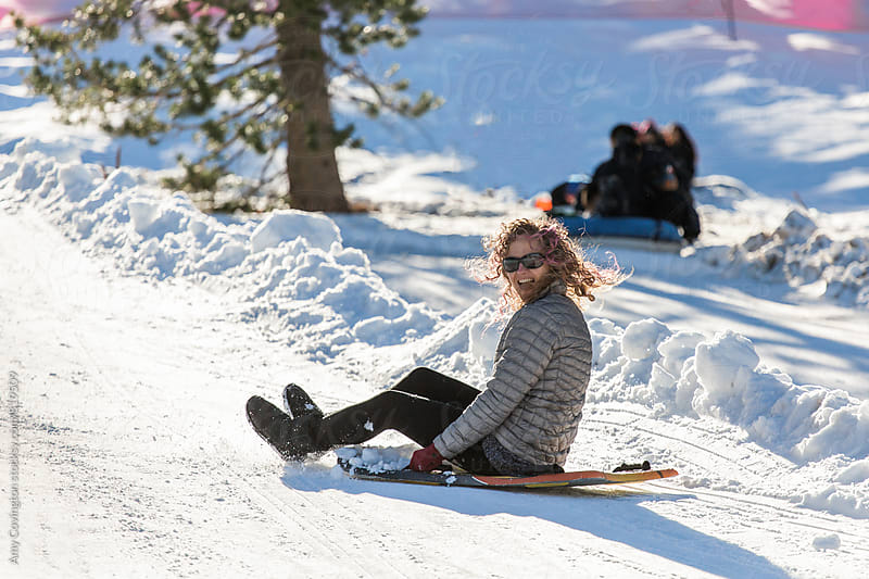 Woman sledding down a hill  by Amy Covington for Stocksy United