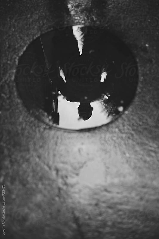 Man puddle reflection by Jovana Rikalo for Stocksy United