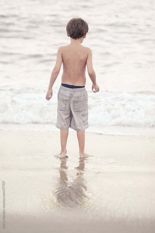 Young boy playing in ocean by Kerry Murphy for Stocksy United