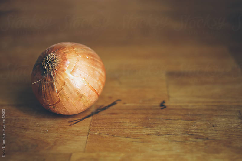 Onion with skin on a wooden board. by Sarah Lalone for Stocksy United