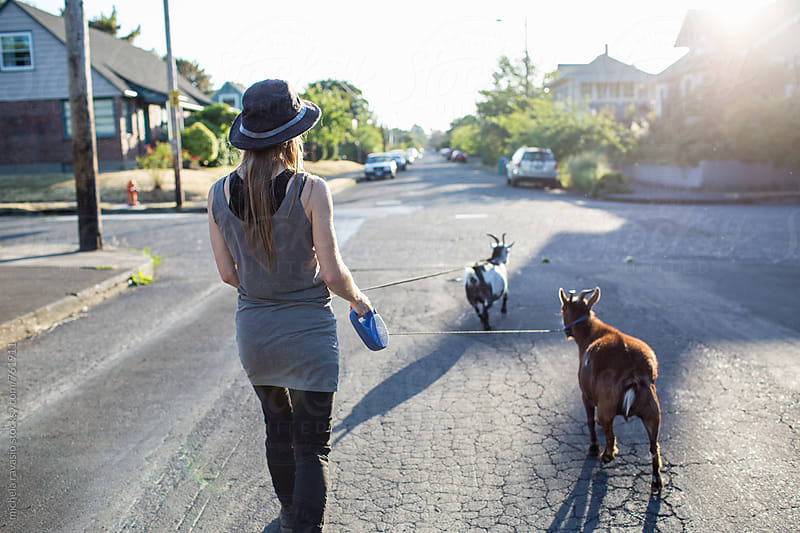 Woman with her two goats coming home from the walk by michela ravasio for Stocksy United