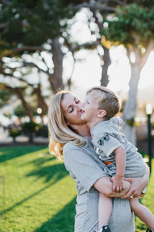 Happy little boy with mother in sunlight by Amir Kaljikovic for Stocksy United
