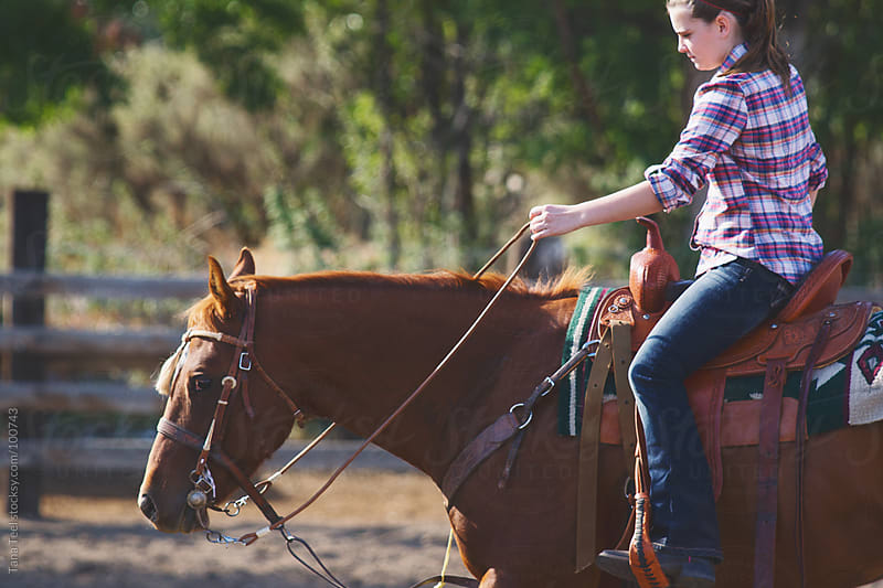 A rider controls her horse using the reins by Tana Teel for Stocksy United