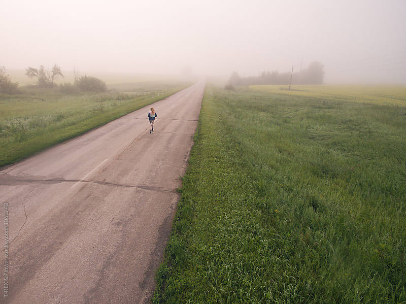 Drone shot of unrecognizable woman running the road in countryside by Danil Nevsky for Stocksy United