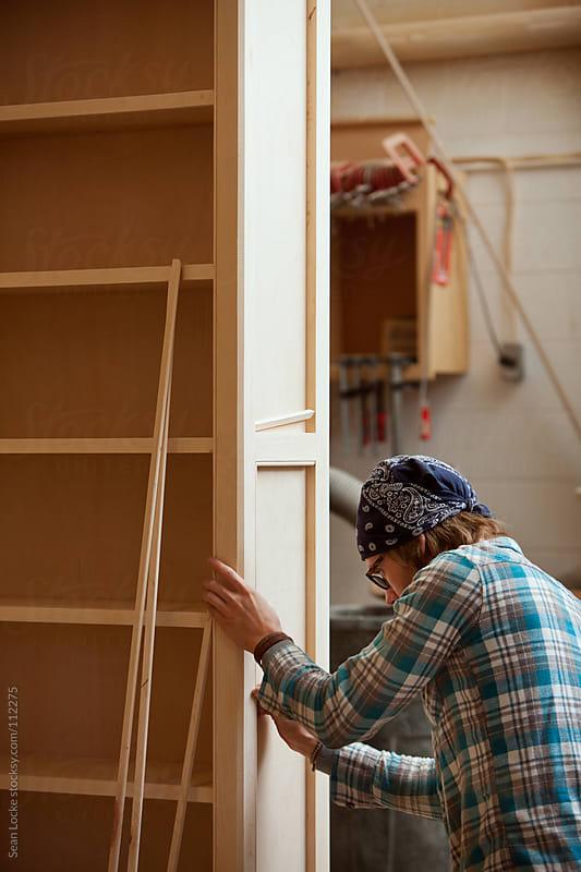Woodworking: Man Putting Trim On Shelf Unit by Sean Locke for Stocksy United