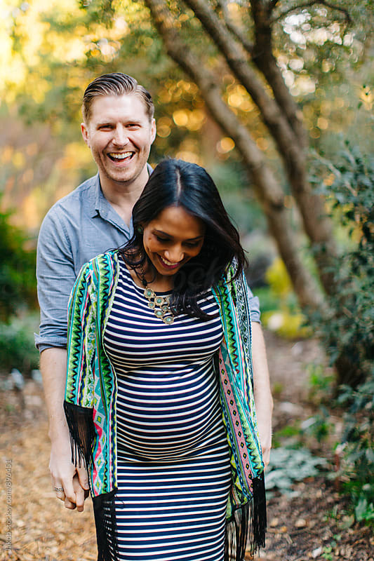Attractive pregnant woman being affectionate with her man in a park by Jakob for Stocksy United