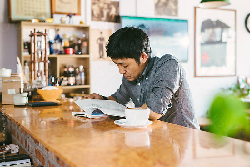 Young man reading at a cafeteria by Maa Hoo for Stocksy United
