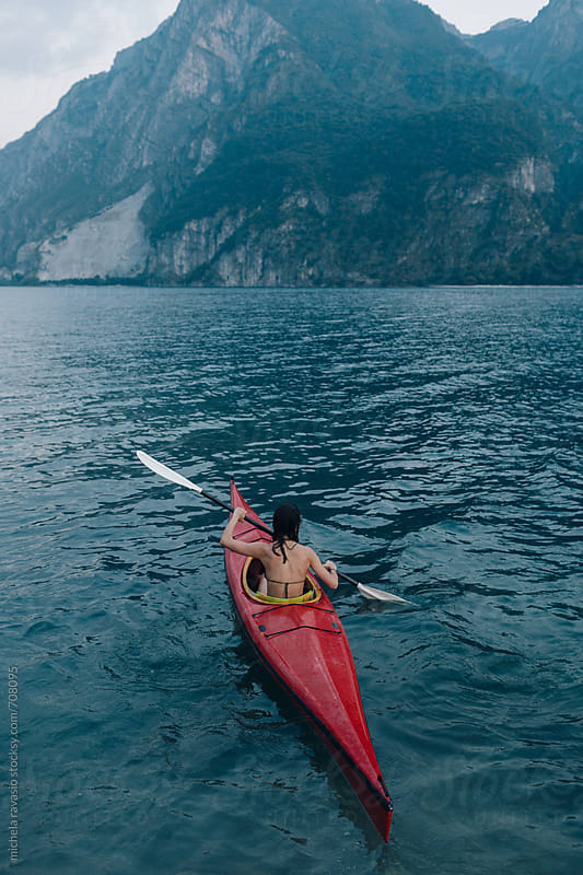 Woman paddling in a canoe on the lake by michela ravasio for Stocksy United