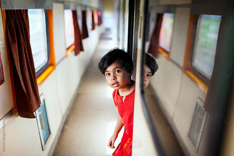 Little girl peeking from behind the door by Saptak Ganguly for Stocksy United