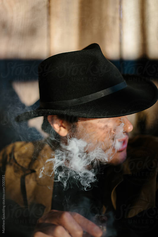 Man in cowboy hat smoking cigar with smoke by Matthew Spaulding for Stocksy United