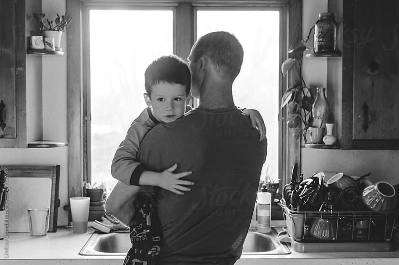 Father holding his young son by the kitchen window by Lindsay Crandall for Stocksy United