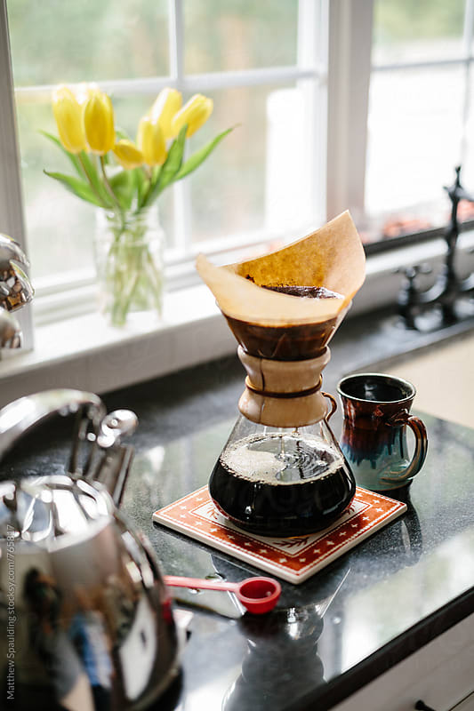 Fresh coffee dripping through filter on kitchen counter by Matthew Spaulding for Stocksy United