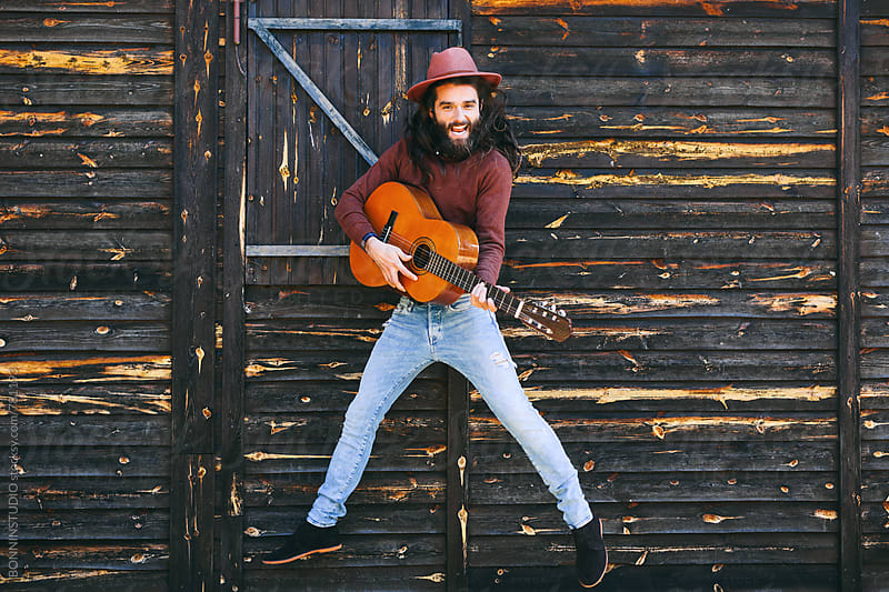 Hipster man holding a guitar whilst jumping in front of a wooden cabin. by BONNINSTUDIO for Stocksy United