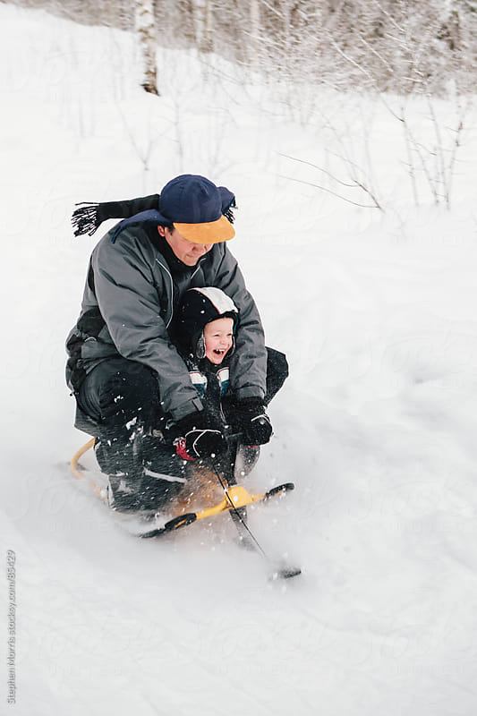 Father and Son Riding Sled Down Hill by Stephen Morris for Stocksy United