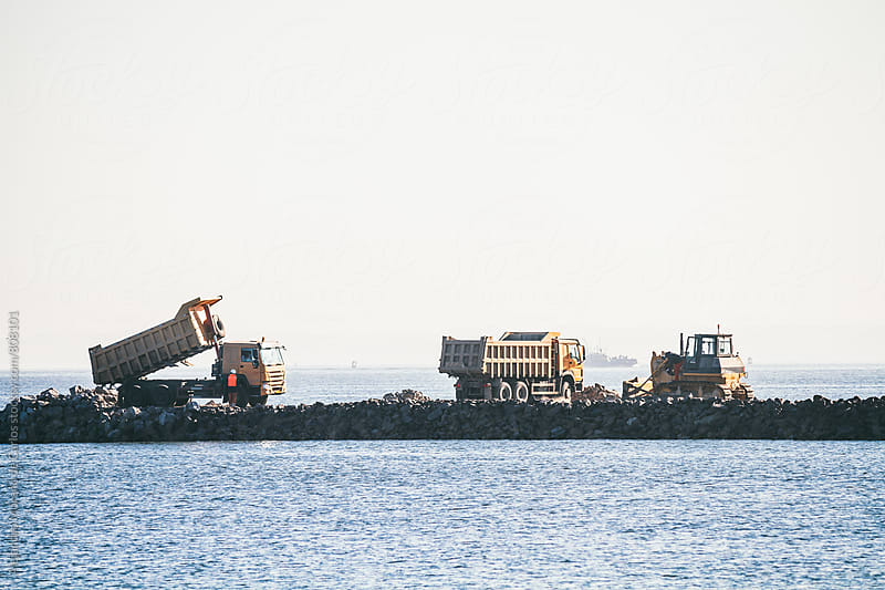 heavy industrial Big trucks dumping rocks in the sea to retrieve land by Alejandro Moreno de Carlos for Stocksy United