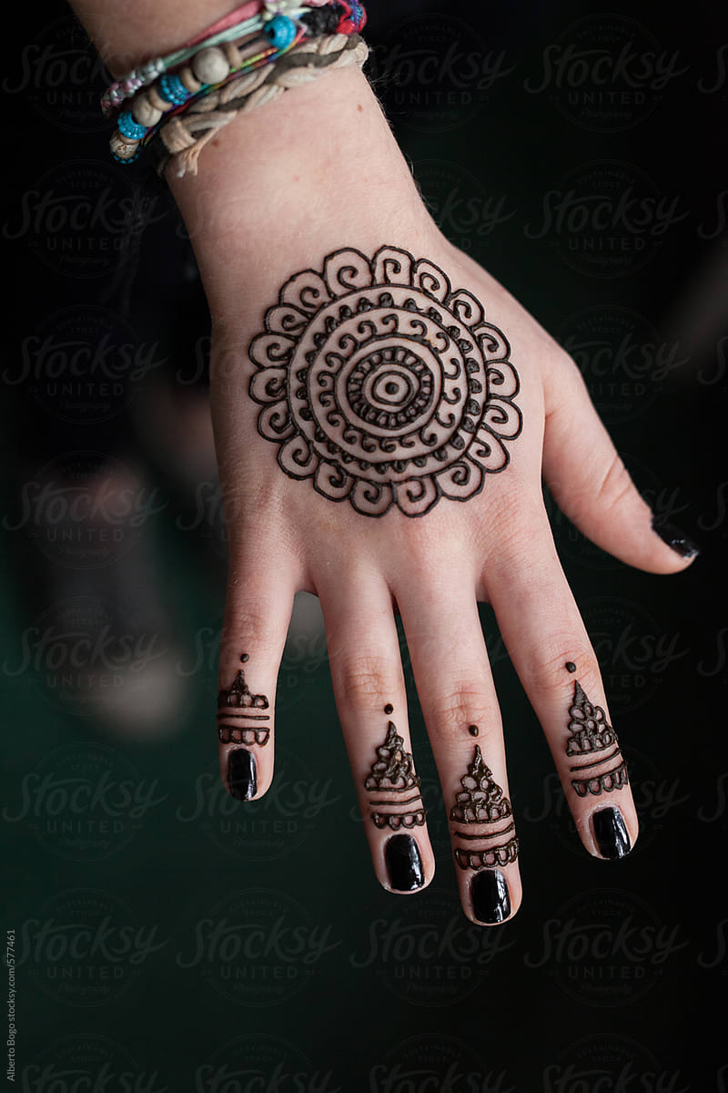 72d7e9dc3 Woman Drawing A Henna Tattoo On A Hand | Stocksy United