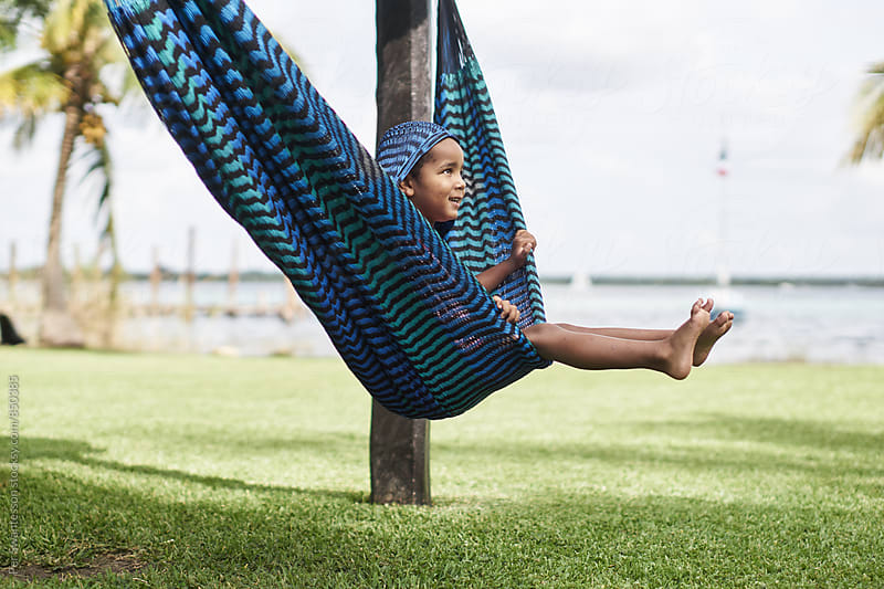 Young boy on vacation swinging in a hammock by Per Swantesson for Stocksy United