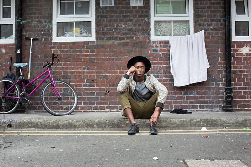 London Street Style - Outdoor Portrait of Young Stylish Grumpy Black Man Sitting on Sidewalk in Rough Neighborhood by Julien L. Balmer for Stocksy United
