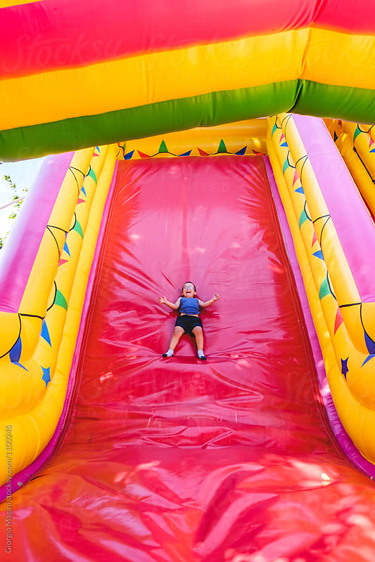 Happy Toddler Boy Having Fun on a Big Inflatable Slide by Giorgio Magini for Stocksy United