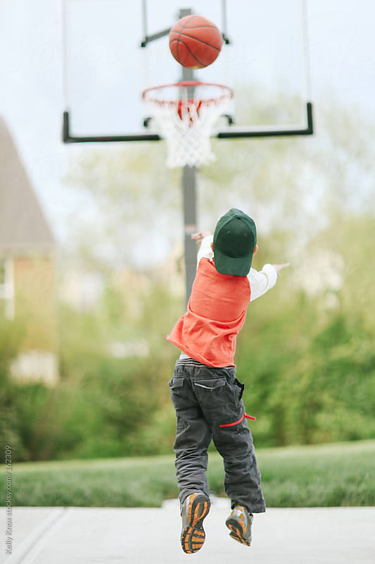 boy shooting a basketball by Kelly Knox for Stocksy United