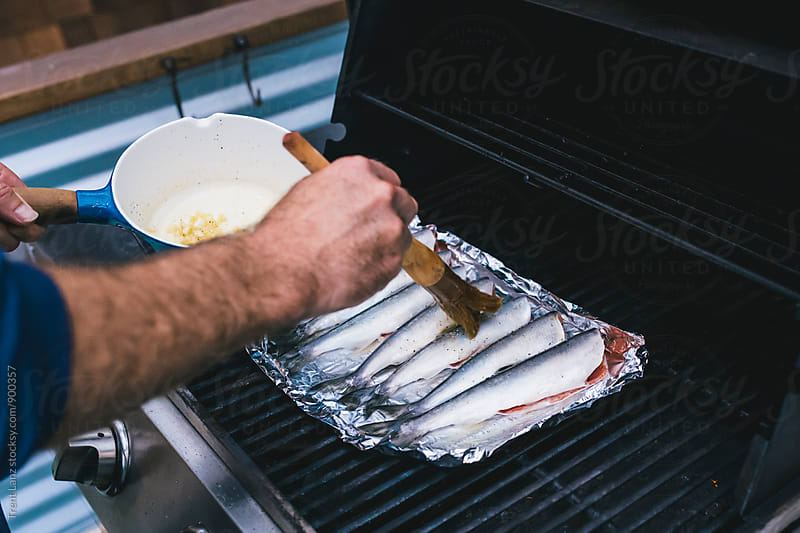 Man's hand smearing fish with seasoning on culinary brush by Trent Lanz for Stocksy United