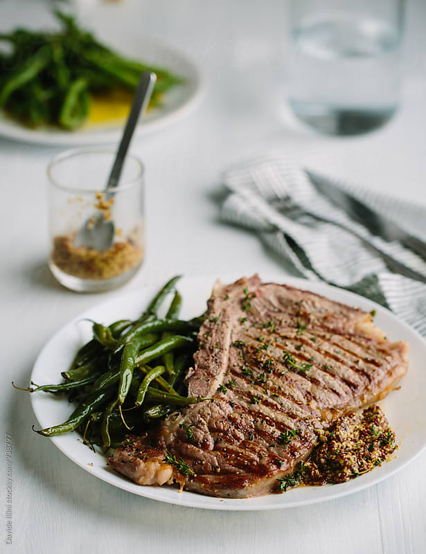 Beef steak with green beans by Davide Illini for Stocksy United