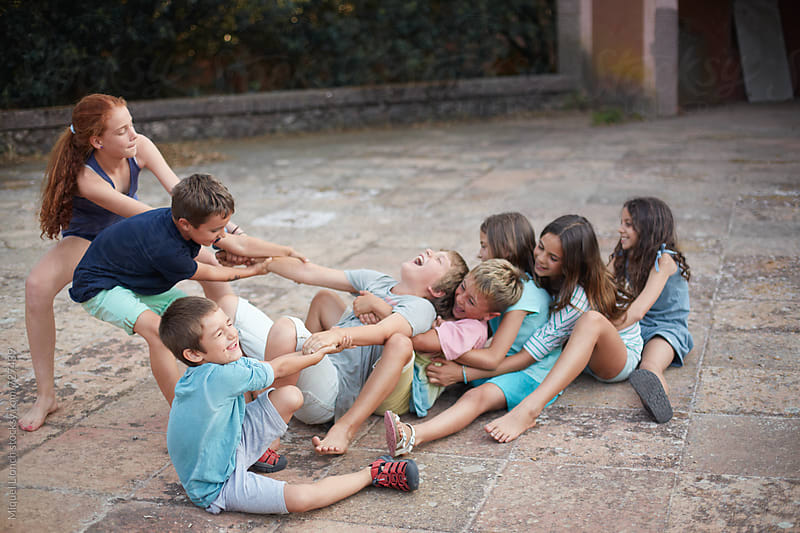 A line of children playing a game of action and strength by Miquel Llonch for Stocksy United
