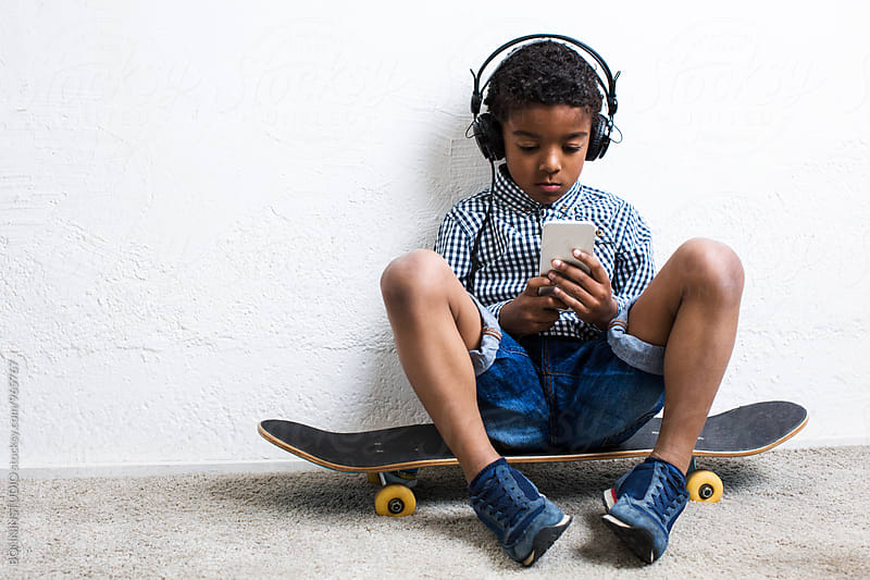 Little boy using smartphone sitting on skateboard. by BONNINSTUDIO for Stocksy United