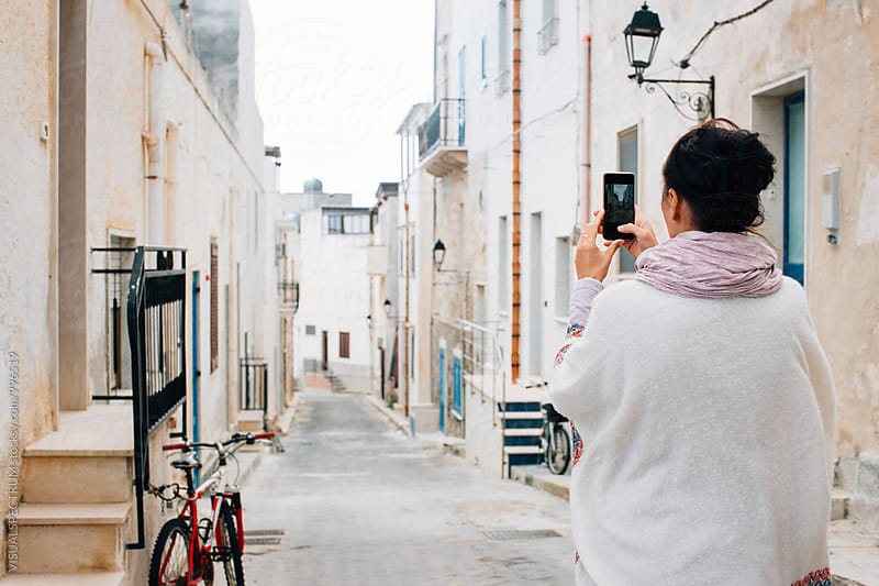 Southern Italy - Brunette in White Poncho Standing in Quaint Whitewashed Village and Taking Smartphone Photo by VISUALSPECTRUM for Stocksy United