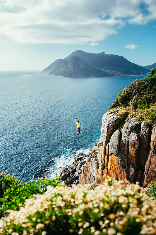 Man tightrope walking between cliffs overlooking the sea by Micky Wiswedel for Stocksy United