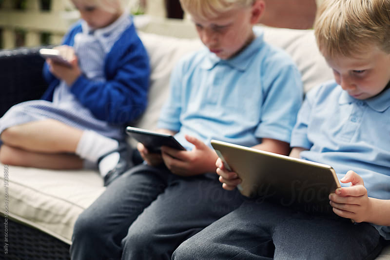 School children using tablets and a smart phone by sally anscombe for Stocksy United