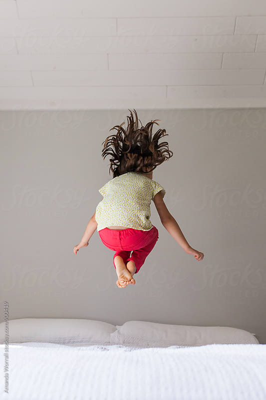 Unrecoginizable young girl wearing bright clothing jumping on a bed in a neutral bedroom by Amanda Worrall for Stocksy United
