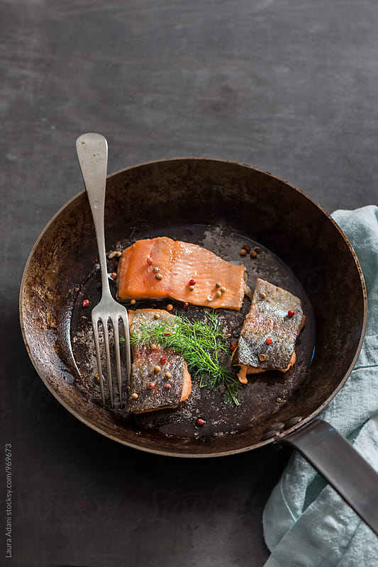 Fillet of trout in an iron pan by Laura Adani for Stocksy United