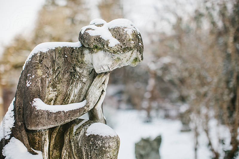 Old statue in a snow-covered cemetery by Zocky for Stocksy United