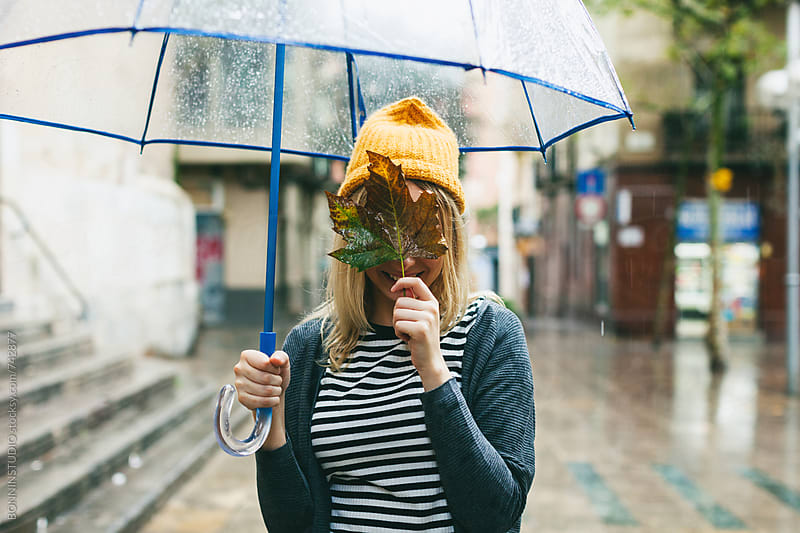 Woman covering her face with a leaf in a rainy day. by BONNINSTUDIO for Stocksy United