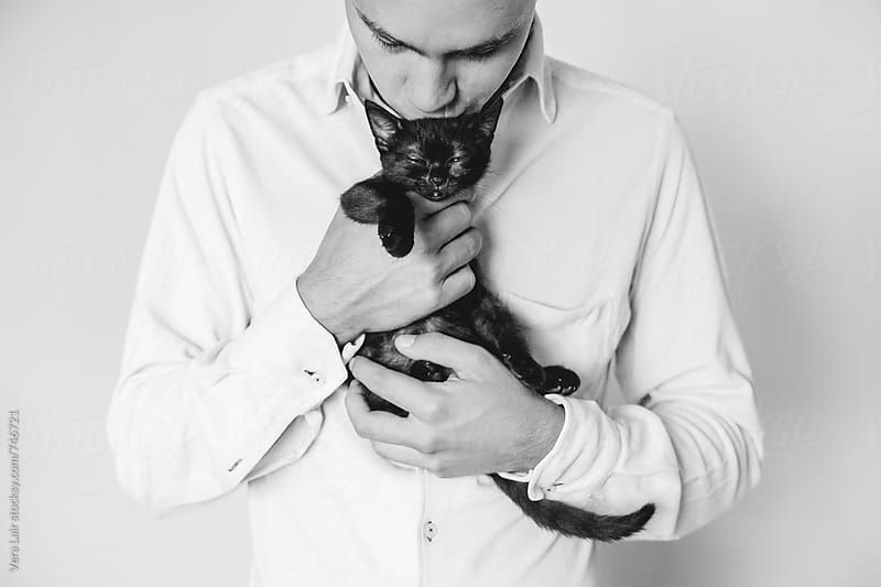 Man kissing a black kitten by Vera Lair for Stocksy United