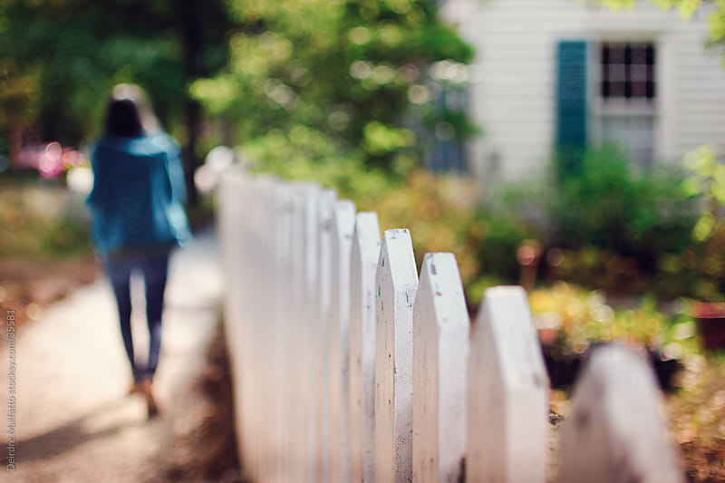 A white picket fence with a garden by Deirdre Malfatto for Stocksy United