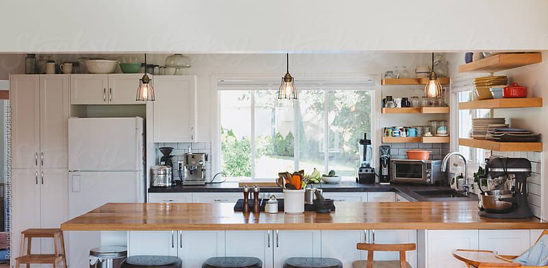Panoramic view of bright, modern kitchen with open concept by Rob and Julia Campbell for Stocksy United