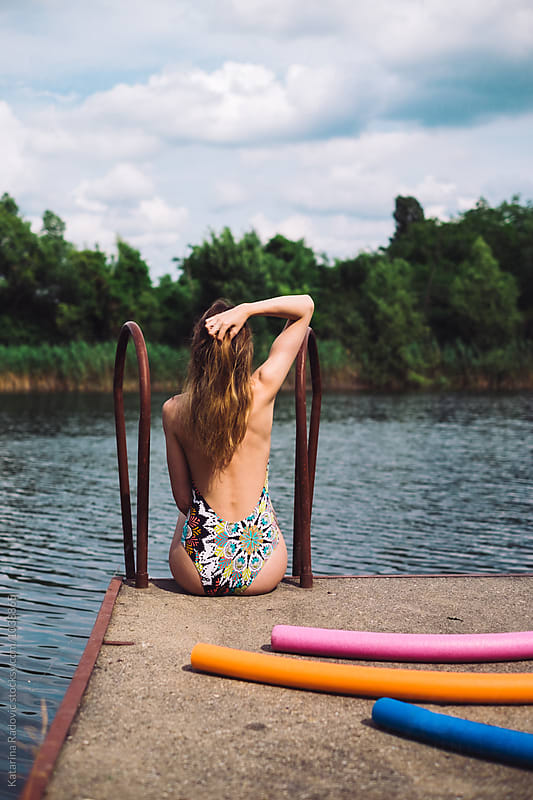 Woman Sitting on a Dock and Getting Tanned by Katarina Radovic for Stocksy United